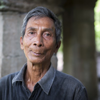 "Khmer stone mason 68 year old Mok Ngam was trained by the French in the 1960's in the art of being a stone mason.  He is one of the few who managed to survive the Khmer Rouge period in Cambodian history.  He had to hide all the language and mason skills he had learnt and assumed the role of a simple peasant in order to survive. Photographed at Banteay Chhmar Temple in Cambodia. Built by Khmer King Jayavarman 7th (1181-1219).  they have spent the last 3 years painstakingly dismatling and rebuilding this 20 metre section of the temple ruins at Banteay Chhmar. John Sanday ""The Khmer stone masons have an affinity with the stone. They're allways touching it feeling for the accuracy of the join.:"