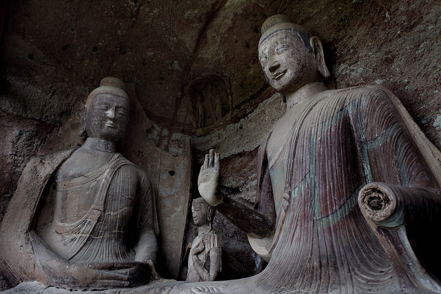 Two spectacular buddhas tower over the statue of a bodhisattva in one of Maijishan's many grottoes. Though once brilliantly colored, most of these statues have not received conservation in centuries and have faded over time. ©Maijishan Grotto Art Institute and Global Heritage Fund